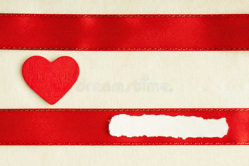 Valentines day background. Red satin ribbon and heart. Valentines day background. Red satin ribbon with wooden heart on cloth. Copy space for text royalty free stock image
