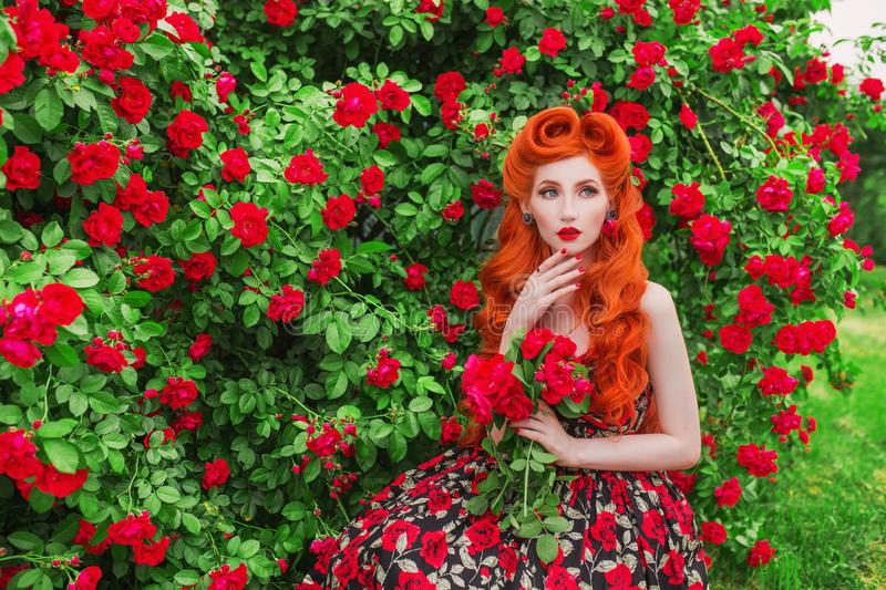 Valentines Day background. Retro girl with red lips in stylish dress with print of roses in beautiful summer garden. Valentines Da. Y beauty redhead model with stock photo