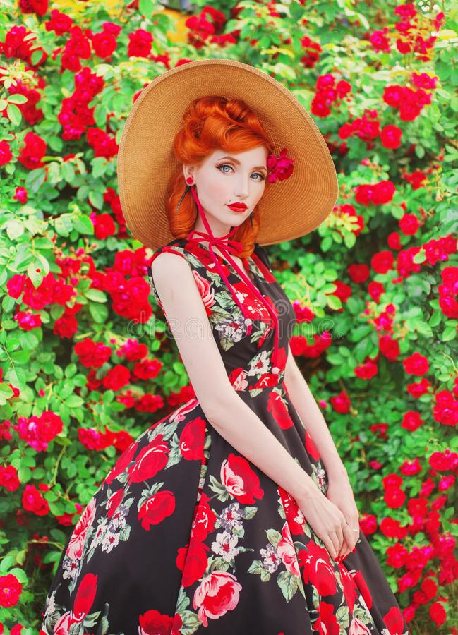 Valentines Day background. Retro girl with red lips in stylish dress with a print of roses in a beautiful summer garden. Valentine stock photo