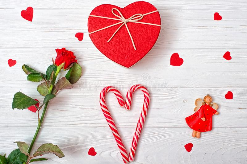 Valentines Day background with a sweet caramel heart, a red rose and the angel. stock image