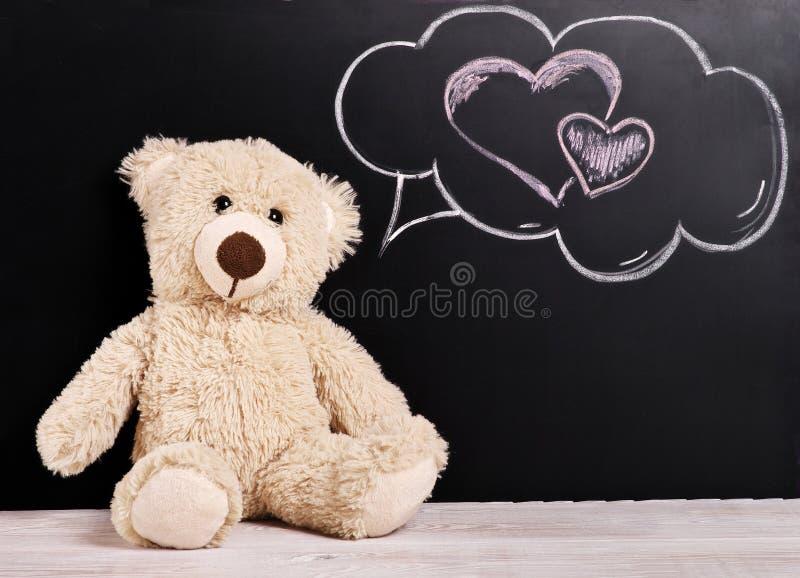 Valentines day background Teddy bear. Teddy bear, valentines day background Teddy with thoughts of love near the chalk Board royalty free stock image