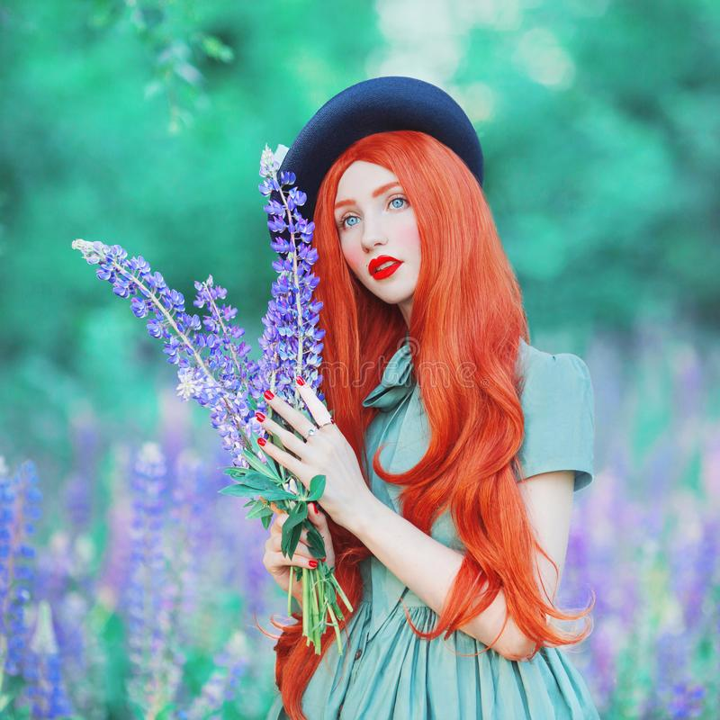 Valentines Day background. Young fairy redhead girl with very long hair on lupine background. Valentines Day beauty woman in mint stock photography