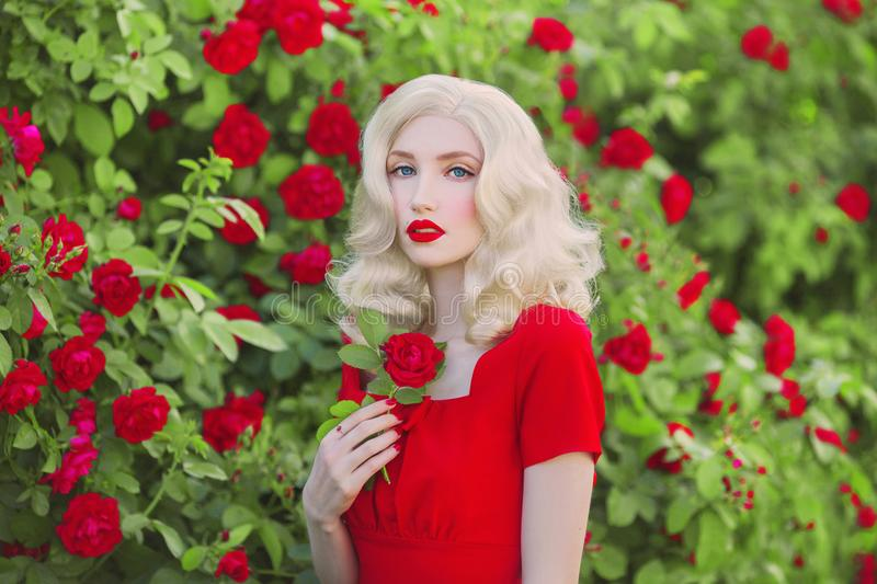 Valentines Day background. Young retro girl with red lips in stylish dress in beautiful summer roses garden. Valentines Day b royalty free stock images