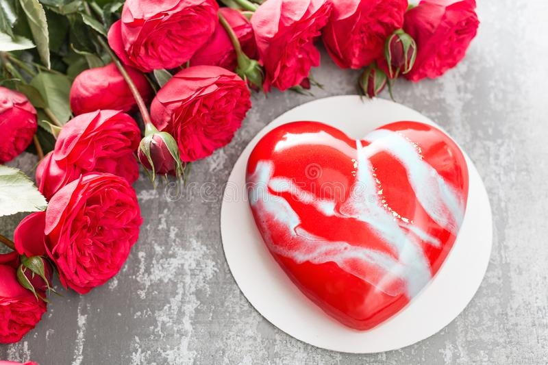 Valentines day or birthday greeting card. Cake in the form of a red heart. Red roses and dessert on vintage wooden table royalty free stock photos