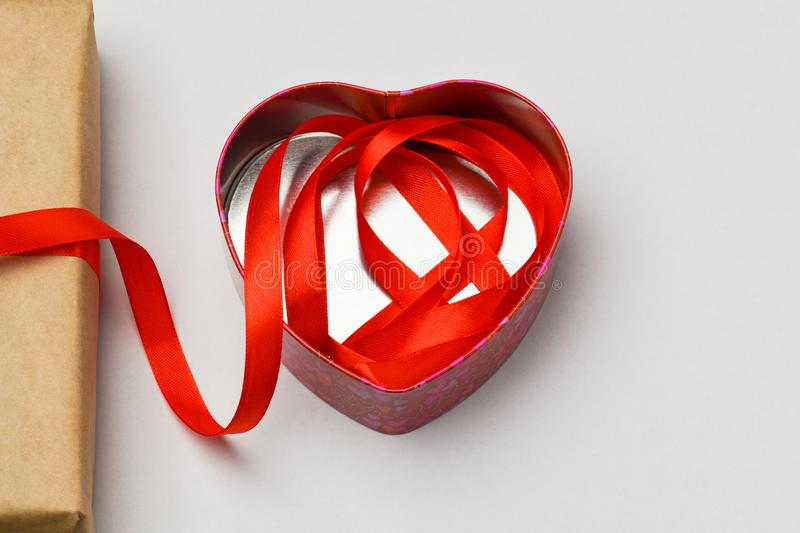 Valentines day . Box in the shape of a heart lies on a gray background and in it lay a red ribbon from the box stock images