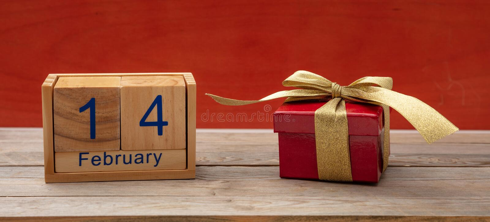 Valentines day. Calendar wooden cubes, 14 February and a gift box on wooden table, red wall royalty free stock photos