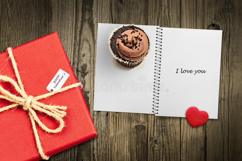 Valentines day card background with red present gift box on wooden table next to chocolate cupcake love heart shape cookie and royalty free stock photo