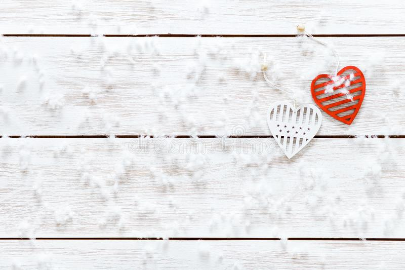 Valentines Day card concept, snowflakes two white red hearts on light wooden table covered with snow, romantic holiday background royalty free stock photo