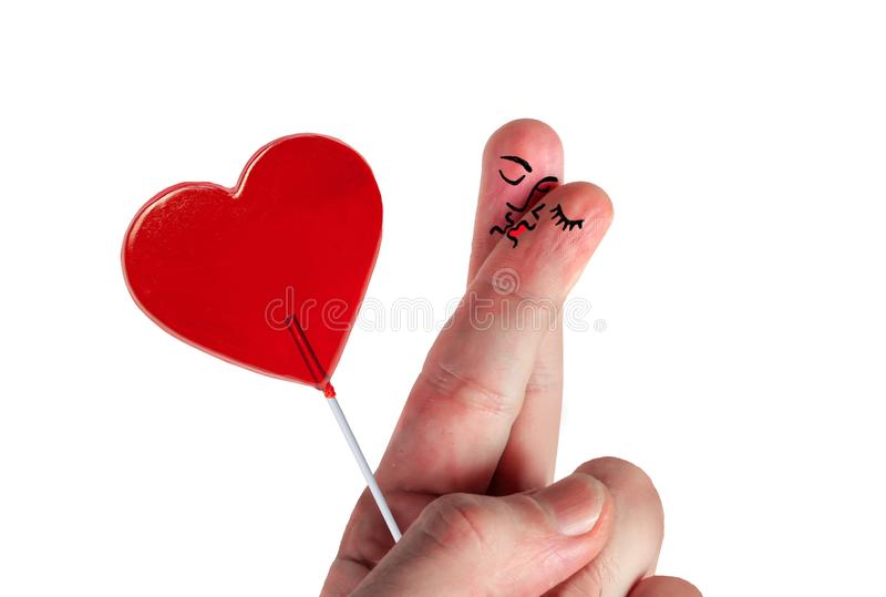 Valentines day card featuring hand with two fingers together painted as man and woman face kissing each other holding love heart. Shape lollipop like royalty free stock images