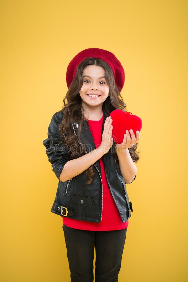 Valentines day. child on yellow backdrop. small girl kid with long curly hair. happy girl in beret leather jacket. Parisian fashion girl hold red heart. world royalty free stock photography