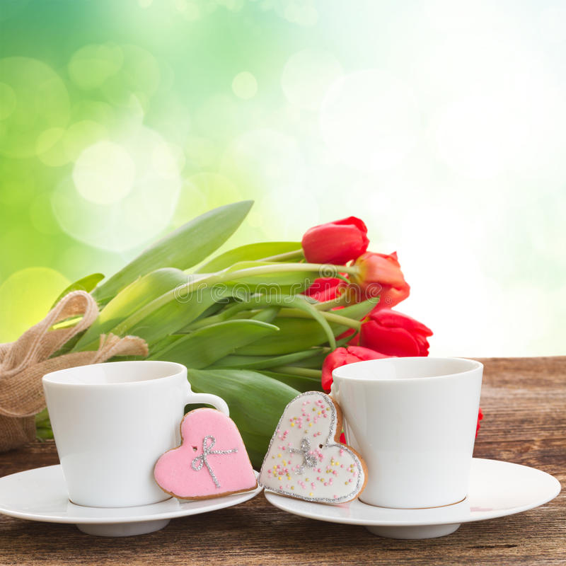 Valentines day coffee. With fresh tulips and cookies on wooden table over garden background royalty free stock photo