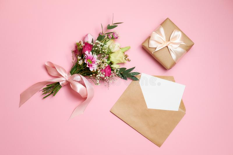 Valentines day composition: bouquet of flowers, gift box with ribbon bow, kraft envelope with greeting card lay at pink background. Woman`s day card template royalty free stock photo