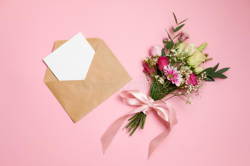 Valentines day composition: bouquet of flowers, kraft envelope with greeting card lay at pink background. Woman`s day card templa. Te, flat layout, top view stock image