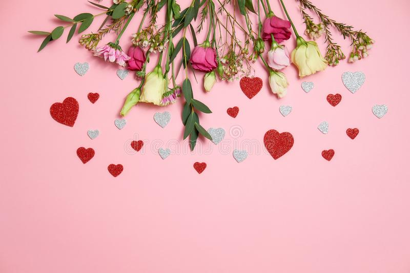 Valentines day composition : flowers and heart shaped valentines card confetti lay on top border on pink background. Love concept. royalty free stock photo