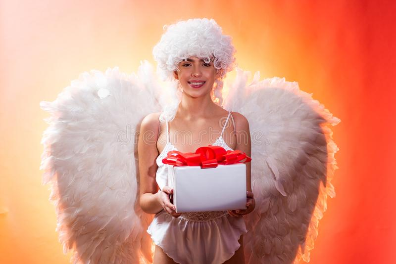 Valentines day concept. Angel with gift. Art photo of a Angelic beautiful woman. Angel woman with feather white wings. And gift. Love concept stock photo
