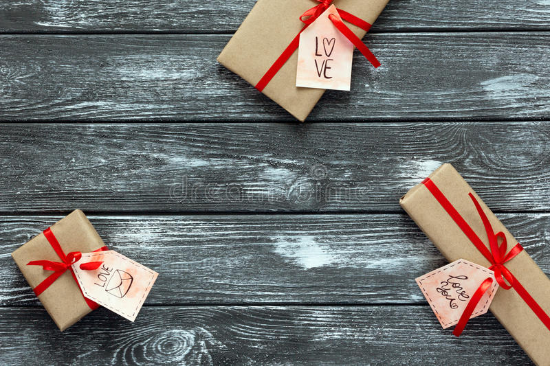 Valentines Day Concept decorated Gift Boxes on grey Wood. Valentines Day Concept wrapped in beige Color Paper and tied up with red Ribbon Gift Boxes of different stock image
