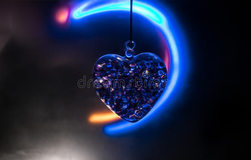 Valentines Day Concept. Glass transparent heart on dark. Crystal heart in the dark, glass heart glows, glass painting, black. Valentines Day Concept. Beautiful stock photos