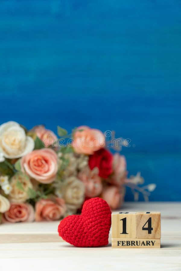 Valentines day concept. hand make yarn red heart beside wooden block calendar set on Valentines date 14 February in front of rose royalty free stock image