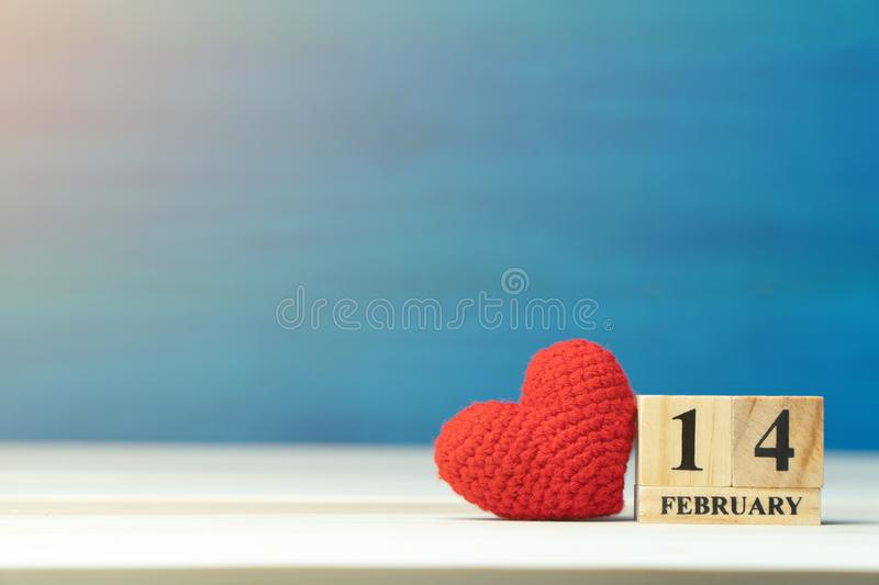 Valentines day concept. hand make yarn red heart beside wooden block calendar set on Valentines date 14 February on wooden table a. Nd blue background stock photos