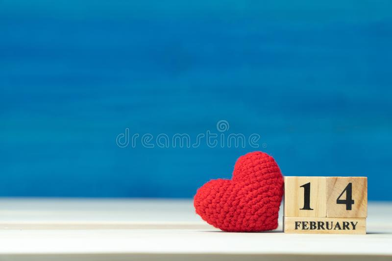 Valentines day concept. hand make yarn red heart beside wooden block calendar set on Valentines date 14 February on wooden table a. Nd blue background stock images