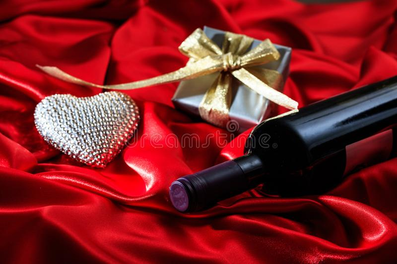 Valentines day. Red wine bottle, a gift and a heart on red satin royalty free stock image