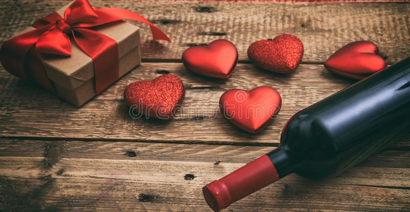 Valentines day. Red wine bottle, a gift and hearts on wooden background royalty free stock image