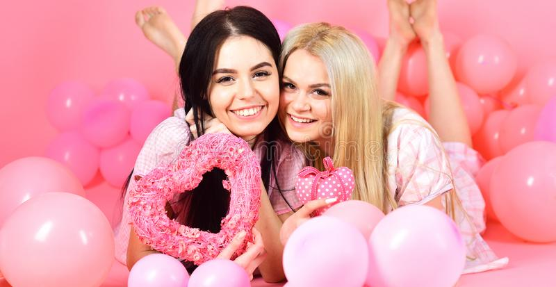 Valentines day concept. Sisters, friends in pajamas at pajamas party. Blonde and brunette on smiling faces dreaming royalty free stock images