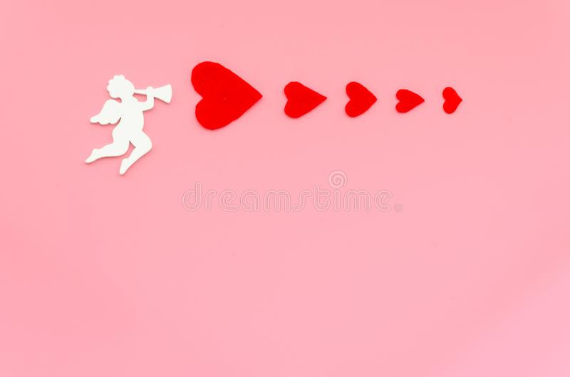 Valentines day concept with white cupid angel shooting with red hearts on a pink background. Copy space for text royalty free stock photos
