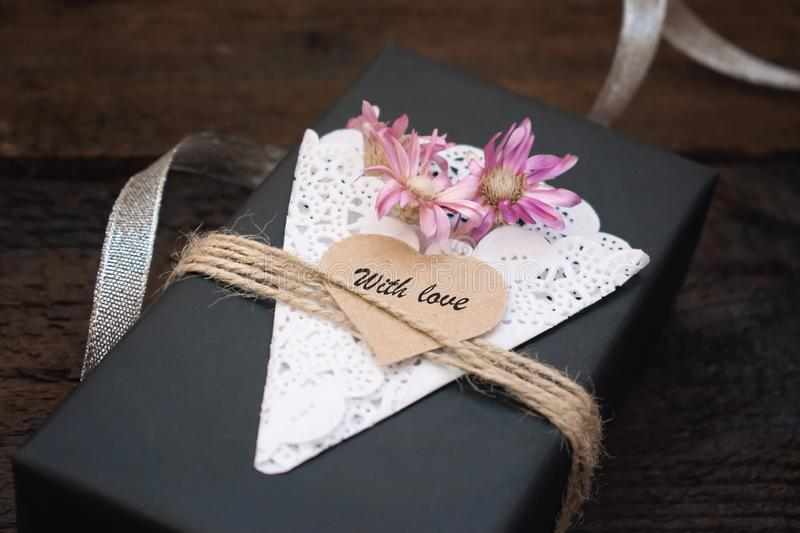 Valentines day gift box ideas. Black paper present box text WITH LOVE on heart, lace napkin, jute rope and silver on dark stock image