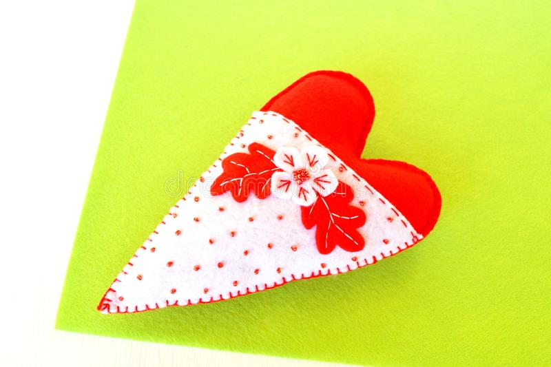 Handmade felt heart - symbol of Valentines Day, felt white and red heart toy on green background. Valentines Day crafts. Felt heart. Valentines Day crafts to royalty free stock photo