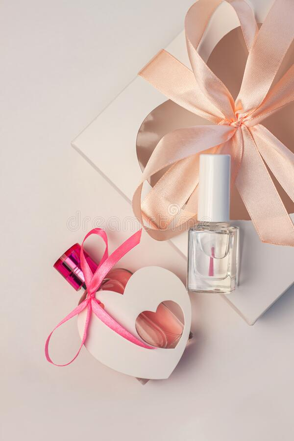 Valentines Day creative concept flatlay. Gift box mockup, pink perfume bottle and nail polish with heart card tag ribbon royalty free stock photo