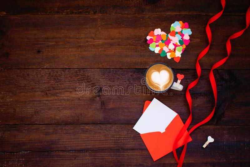 Valentines day creativity, DIY craft gift, card ideas. Many multicolored paper hearts with coffee, red envelope, ribbons on wooden stock photo