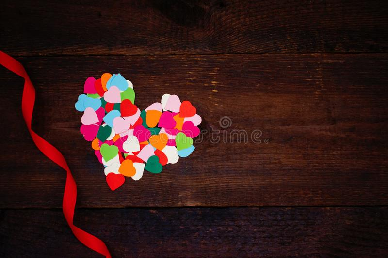 Valentines day creativity, DIY gift, card ideas. Many multicolored paper hearts are poured from glass transparent bottle on stock photos