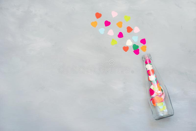 Valentines day creativity, DIY gift, card ideas. Many multicolored paper hearts are poured from glass transparent bottle on royalty free stock images