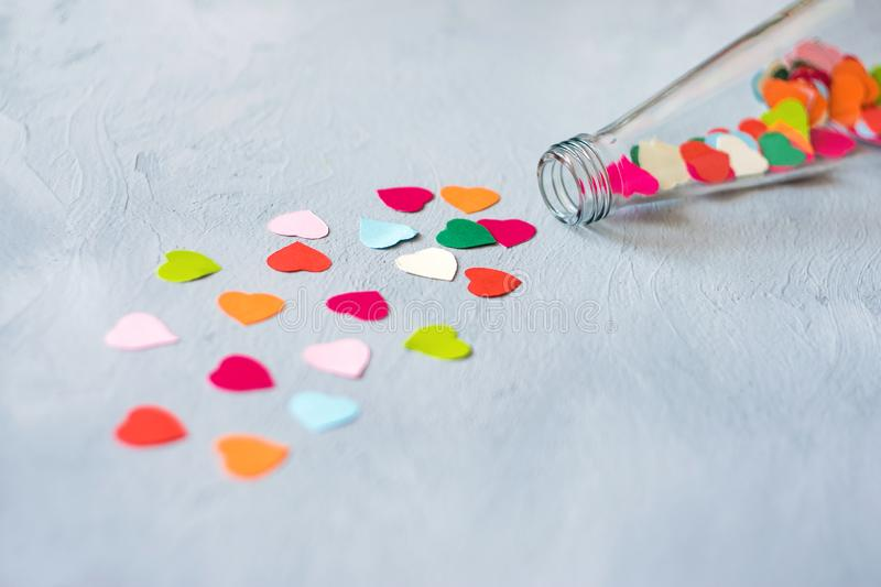 Valentines day creativity, DIY gift, card ideas. Many multicolored paper hearts are poured from glass transparent bottle on stock photography