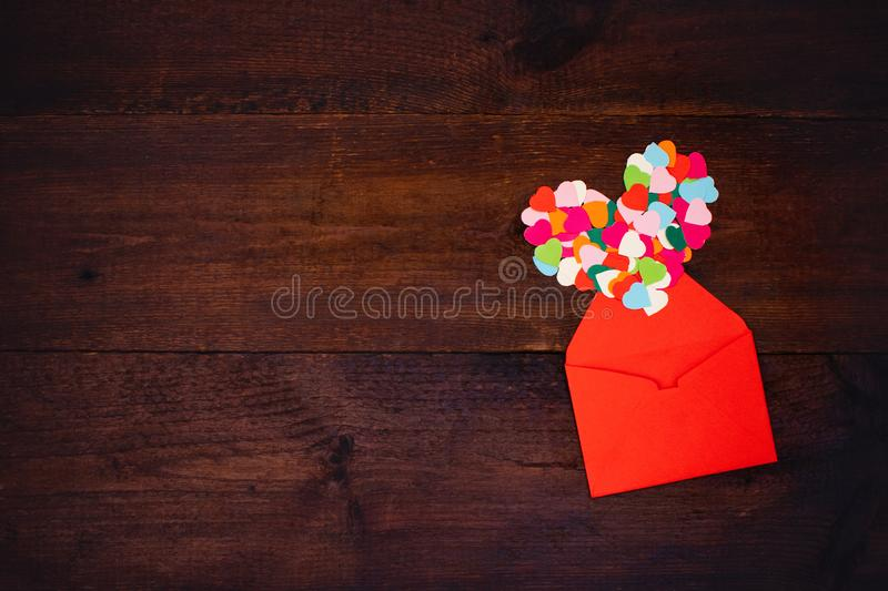 Valentines day creativity, DIY gift, card ideas. Many multicolored paper hearts with red paper envelope on wooden background stock photography