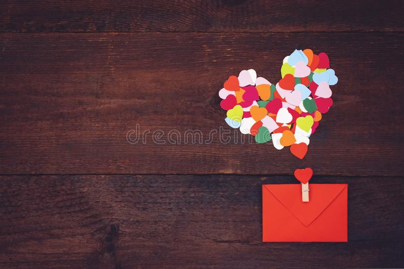 Valentines day creativity, DIY craft gift, card ideas. Many multicolored paper hearts with red paper envelope on wooden background royalty free stock photography
