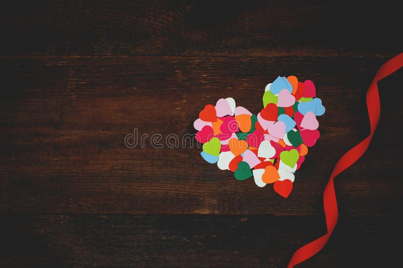 Valentines day creativity, DIY craft gift, card ideas. Many multicolored paper hearts with red ribbons on wooden background. Gift stock photography