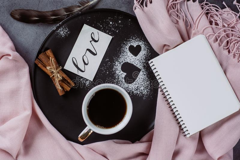 Valentines day with cup of coffee, bumps,skarf, cinnamon and heart on gray table. From above in flat lay style stock photo