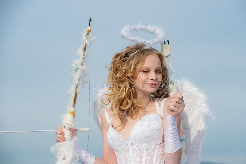 Valentines day cupid. Innocent Girl with angel wings standing with bow and arrow against blue sky and white clouds. Enjoying magic moment. Lovely child stock image