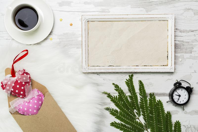 Valentines Day Decoration with white horisontal frame, coffe, alarm clock and envelope with hearts . Flat lay mockup royalty free stock images
