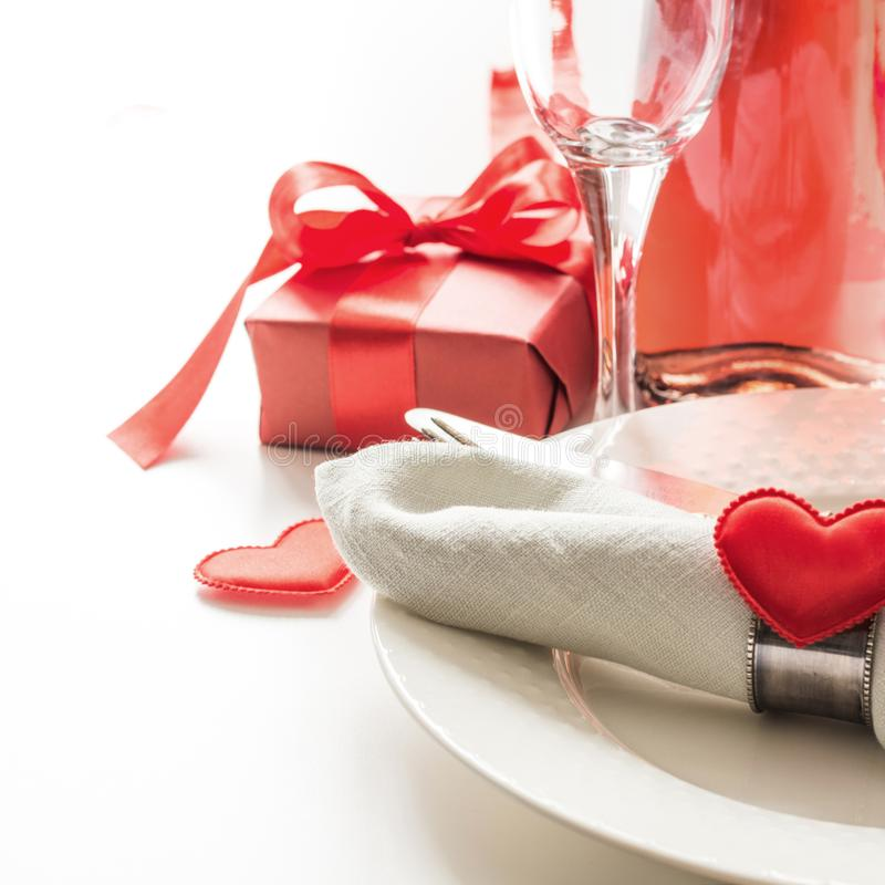 Valentines day dinner with table place setting with red gift, a bottle of champagne, heart ornaments with silverware on white. Clo royalty free stock photos