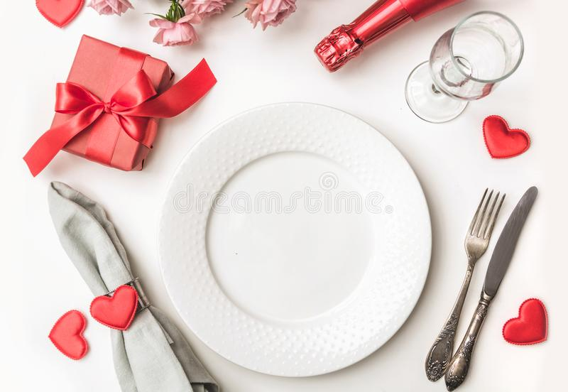 Valentines day dinner with table place setting with red gift, a bottle of champagne, hearts with silverware on white background. V royalty free stock image