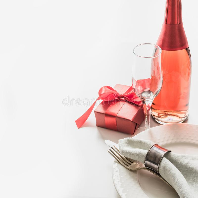 Valentines day dinner with table place setting with red gift, a bottle of champagne on white. Close up. Valentine`s card royalty free stock photo