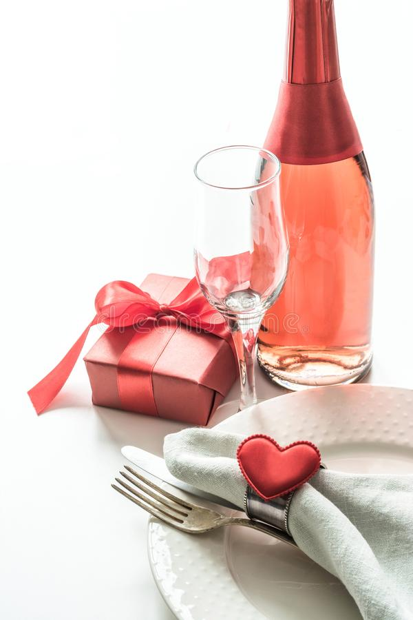Valentines day dinner with table place setting with red gift, glass for champagne, a bottle of champagne, heart ornaments with sil stock photos