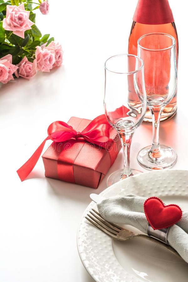 Valentines day dinner with table place setting with red gift, glass for champagne, a bottle of champagne, hearts with silverware o stock photo