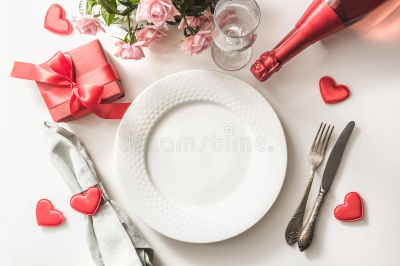 Valentines day dinner with table place setting with red gift, glass for champagne, a bottle of champagne, pink roses, heart orname stock image