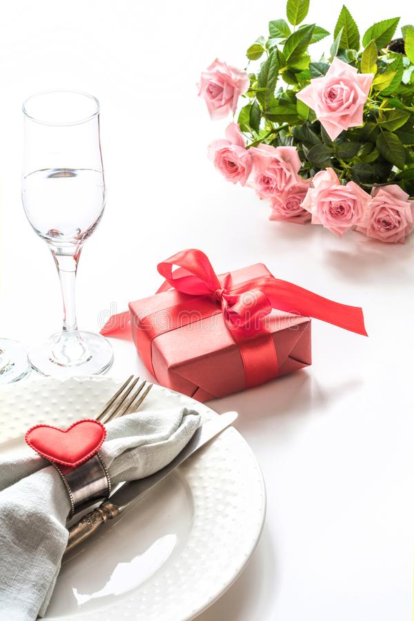 Valentines day dinner with table place setting with red gift, glass for champagne, heart ornaments with silverware. Valentine`s c royalty free stock photo