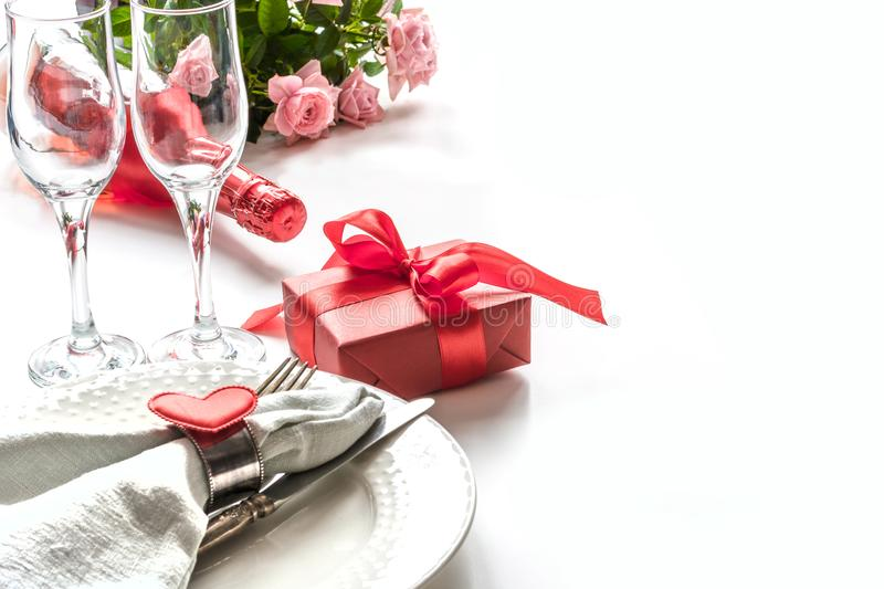 Valentines day dinner with table place setting with red gift, glass for champagne, heart ornaments with silverware on white. Close royalty free stock photos