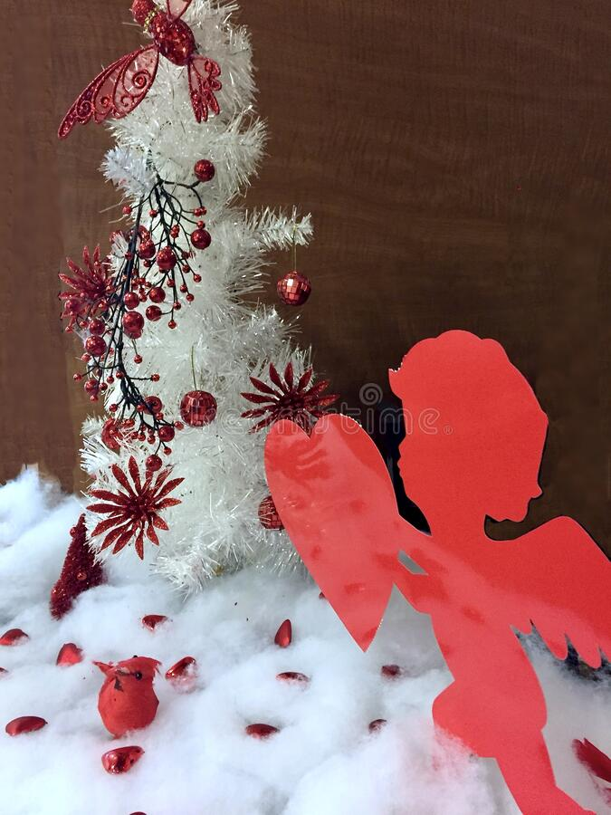 Valentines day display with cupid, red love hearts white snow and small tree. royalty free stock photos